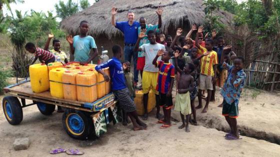 Los rotarios Craig Sorensen y Marty Hatala junto a residentes de la aldea de Adevukope y los recipientes con el primer suministro de agua pura que llega a la comunidad.  Fotografía de: Cortesía de Craig Sorensen